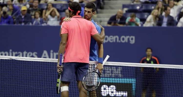 Novak Djokovic, rear, of Serbia, is congratulated by Jo-Wilfried Tsonga, of France, after Tsonga retired from the match in the quarterfinals of the U.S. Open tennis tournament, Tuesday, Sept. 6, 2016, in New York. (AP Photo/Darron Cummings)